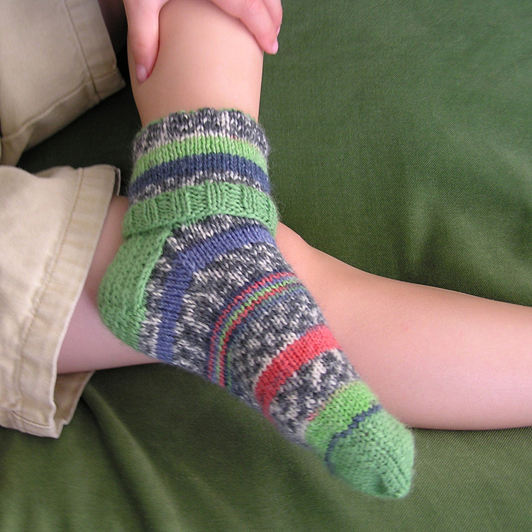 Kids socks pattern featuring a folded over cuff are worked top down with a heel flap and heel turn construction.