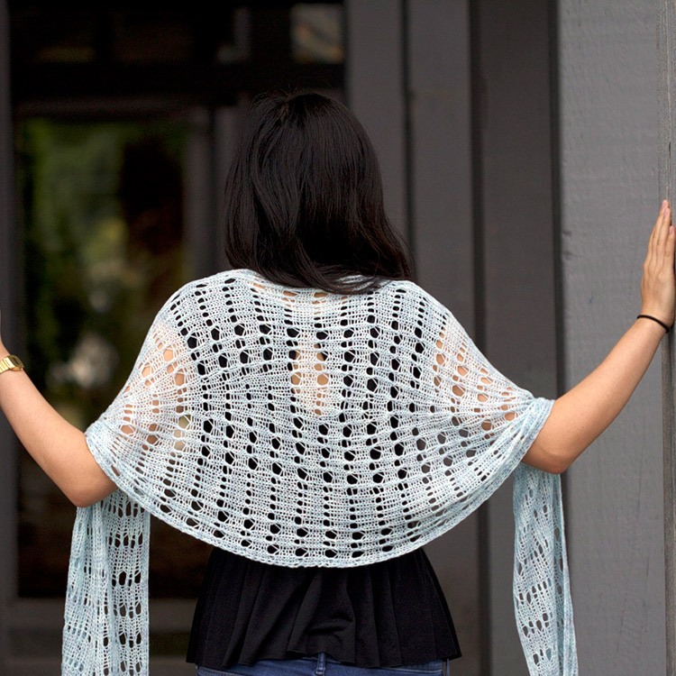 Lace shawl with curving side edges created by increases and decreases.