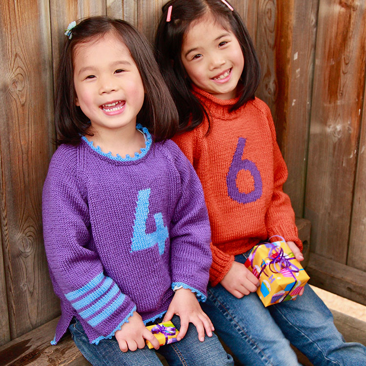 Kids raglan sleeved sweaters with intarsia number on the front and stripes on one sleeve.