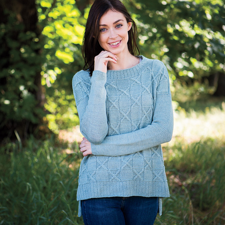 Drop shoulder pullover with split high-low hem and cabled checkerboard pattern.
