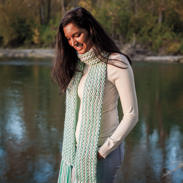 Woman standing in front of a lake looking down and wearing a striped hand knit scarf.