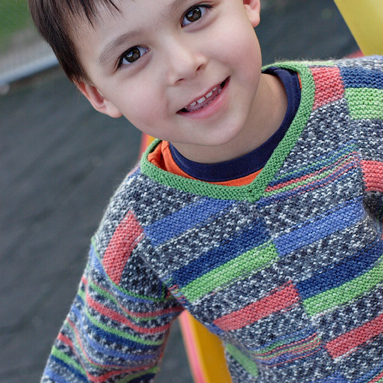 Child's v-neck pullover worked in modular strips with self-patterning yarn.