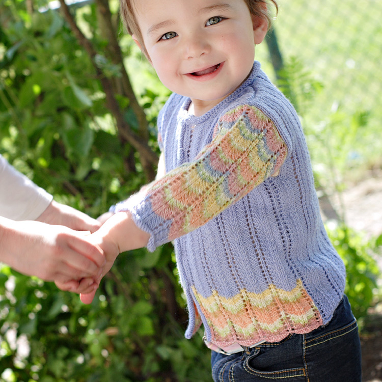 Baby and child lace cardigan with scalloped stripes in self-patterning sock yarn.