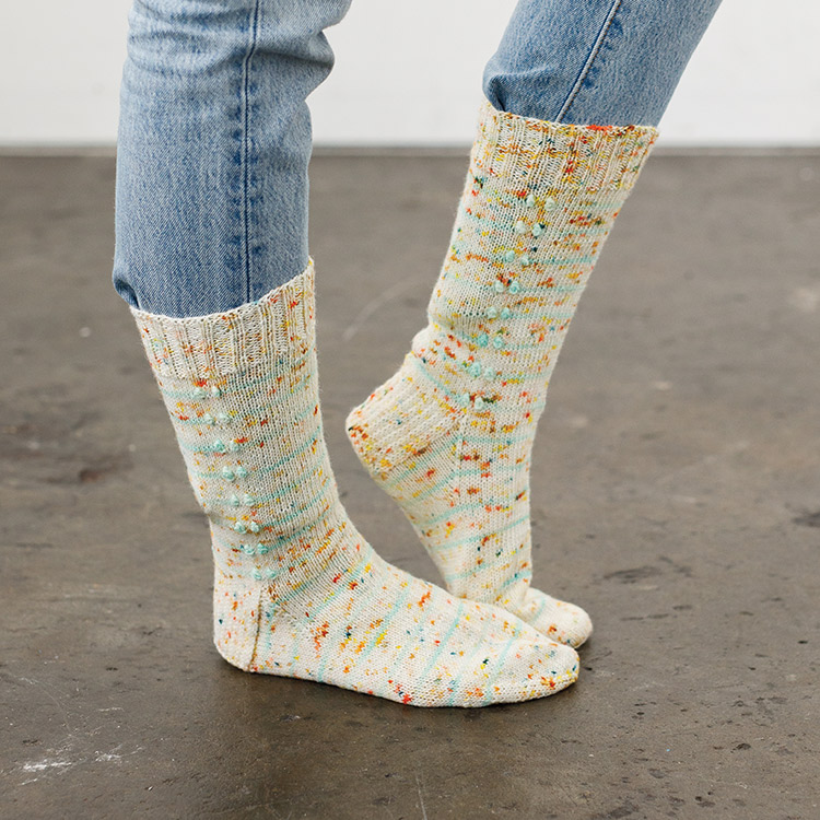 Top down socks with heel flap construction and a double line of tufts/bobbles running down the leg.