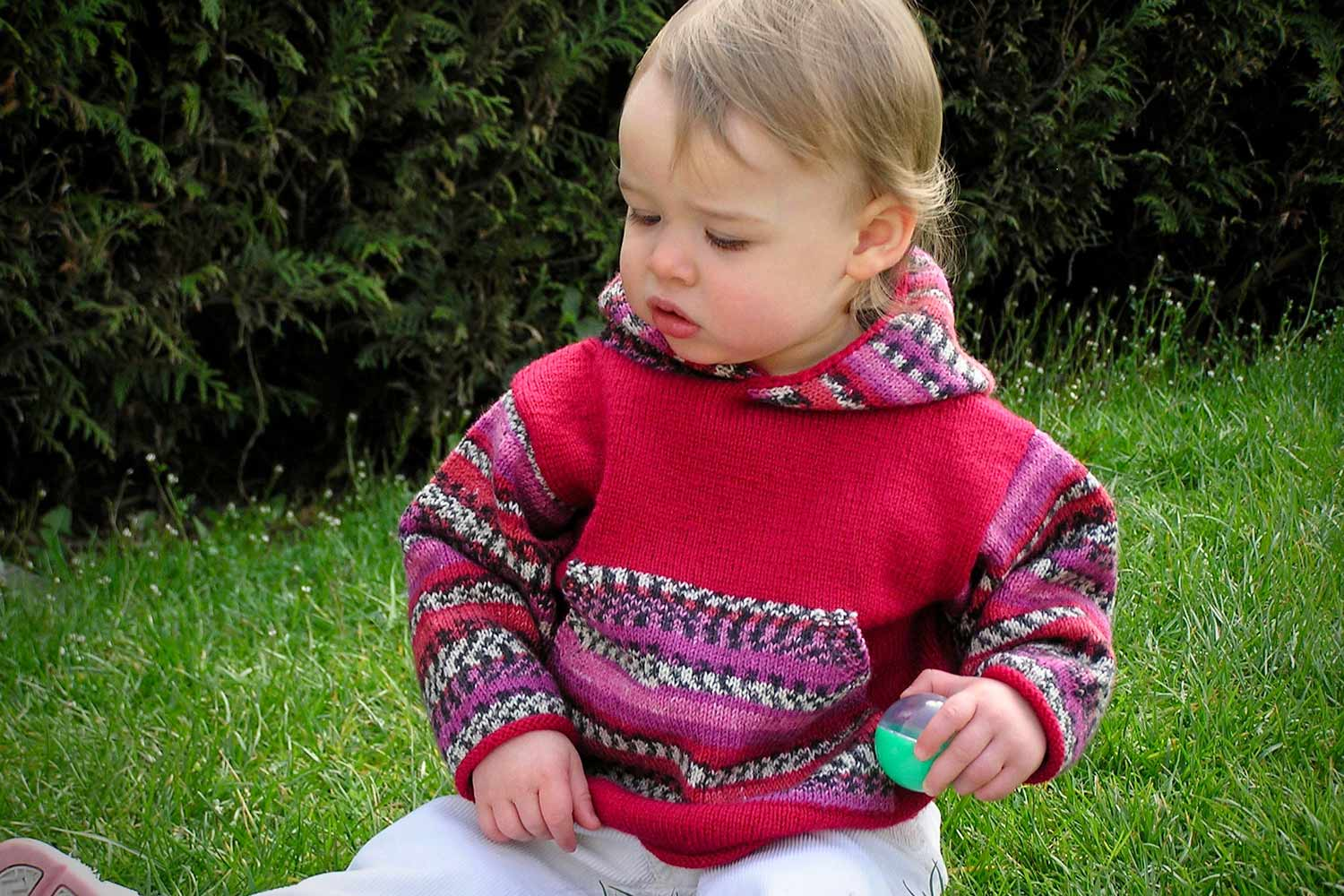Baby seated on grass wearing a red pullover hoodie with sleeves, hood and kangaroo pocket worked in self-patterning yarn.
