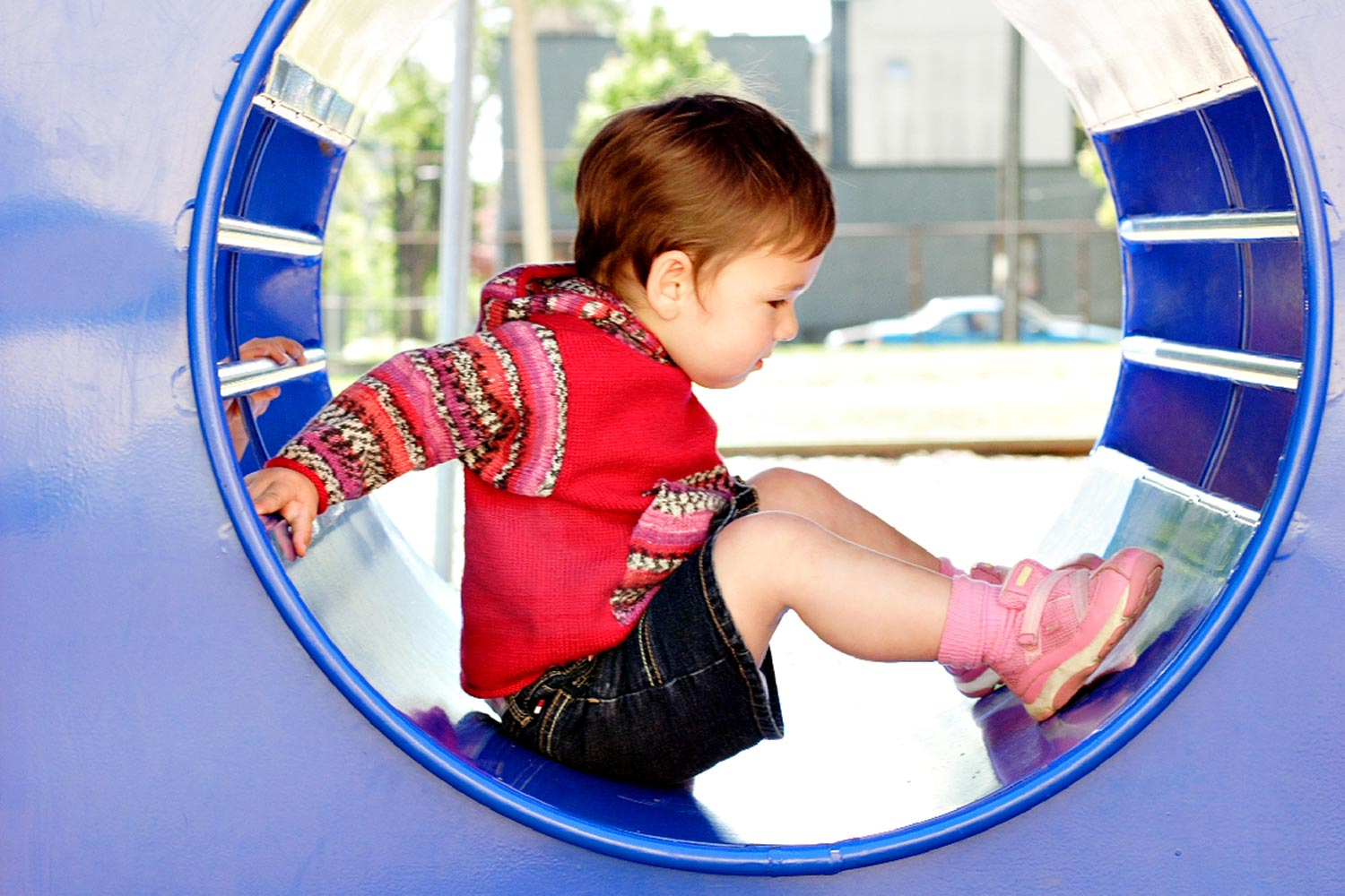 Profile view of toddler seated in a tubular playground structure, wearing a hoodie with sleeves, hood and kangaroo pocket worked in self-patterning yarn.