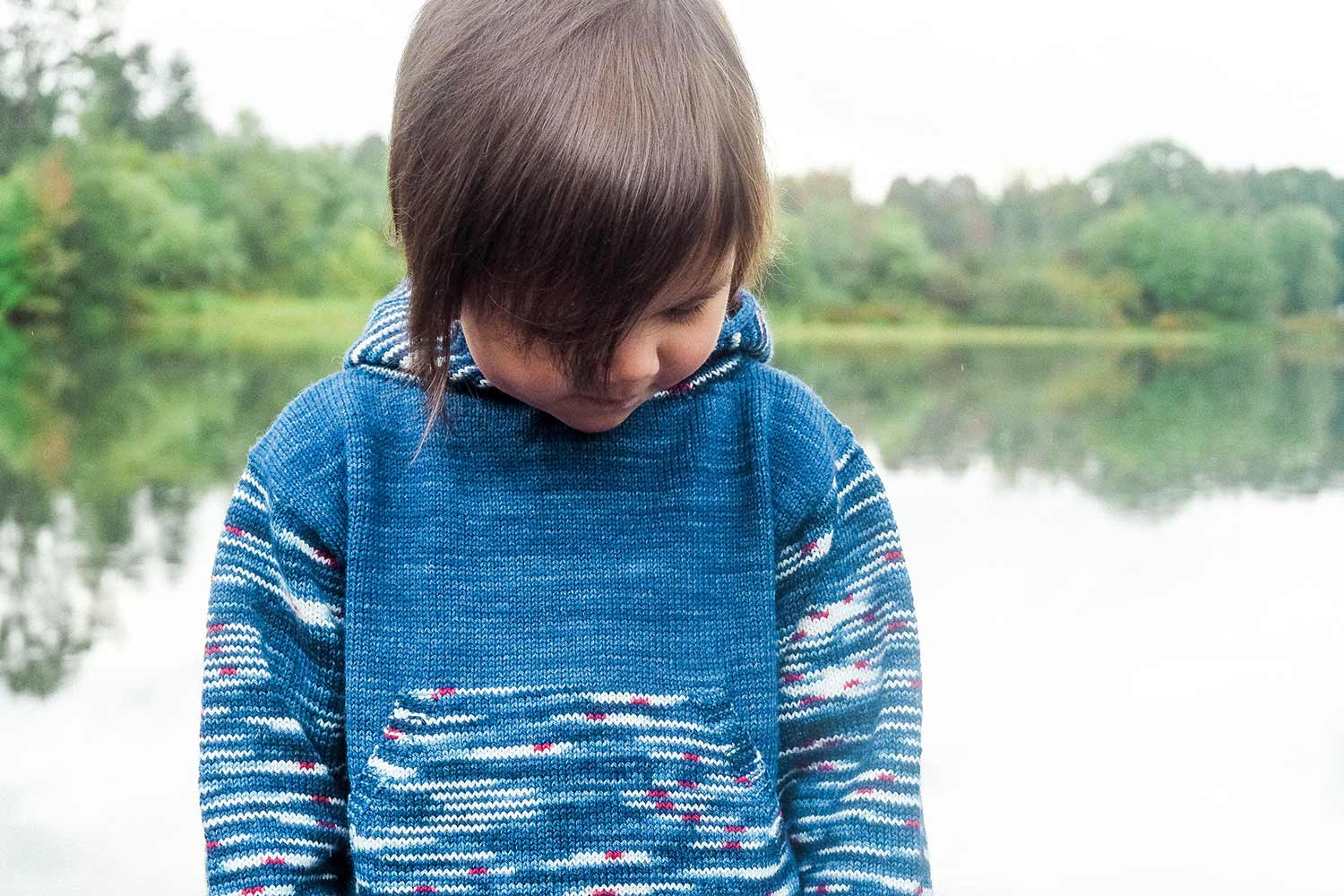 Child standing in front of a lake wearing a blue hoodie with striped sleeves and kangaroo pocket.