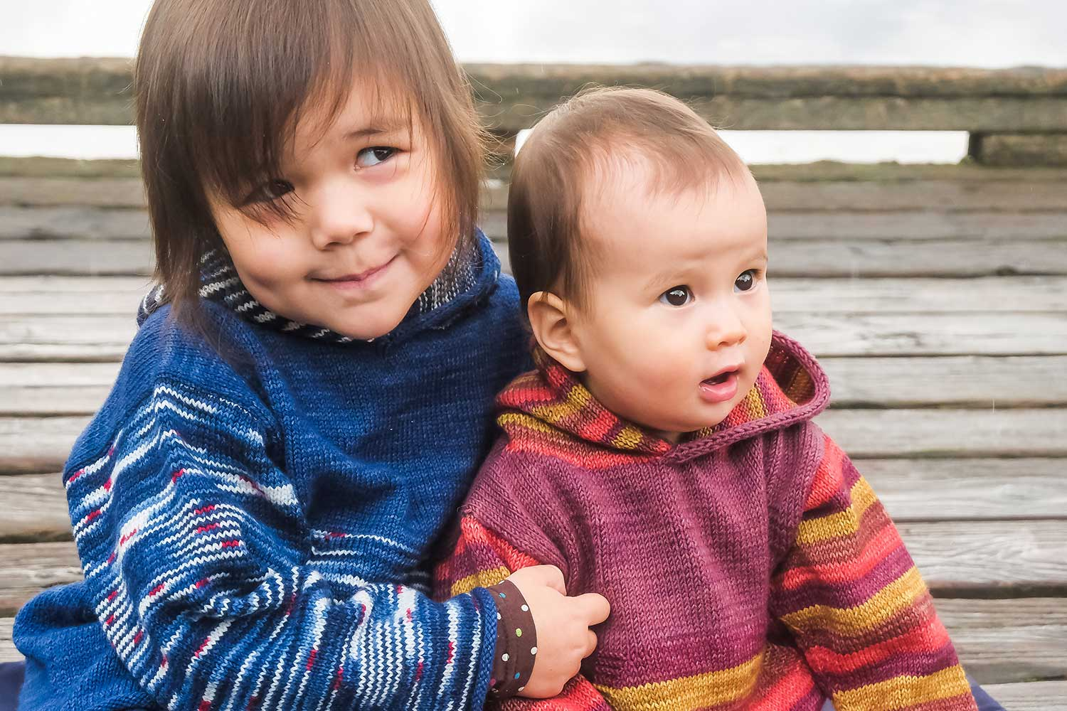 Child and baby seated together on wooden dock wearing handknit hoodies with stripes sleeves and hoods.
