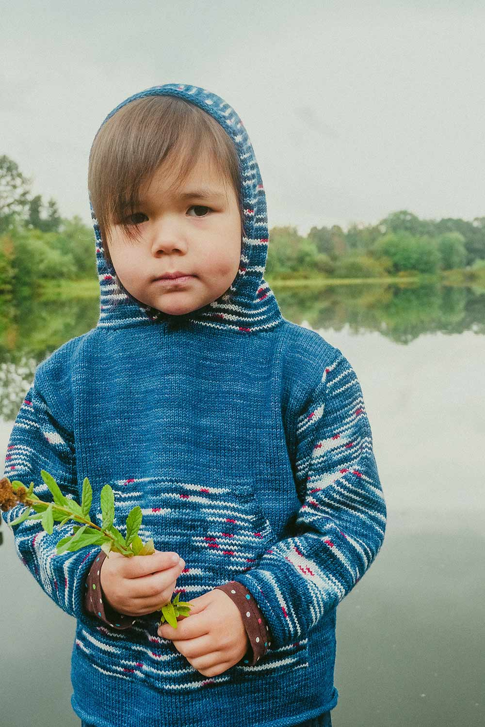 Dimpled child wearing a handknit hoodie with hood up; body is blue and hood, sleeves and kangaroo pocket are striped.