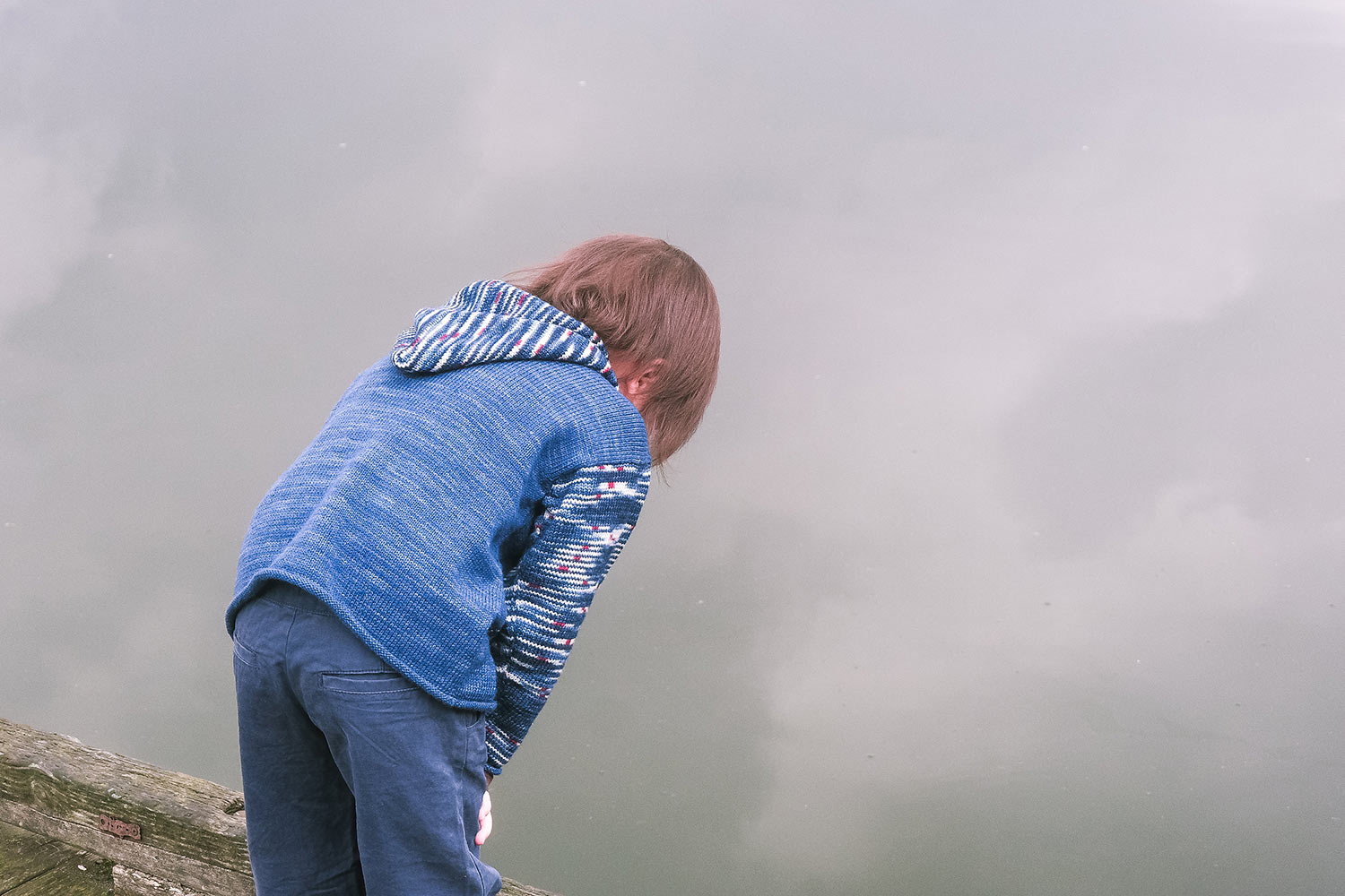 Back view of child looking into water reflecting the cloudy sky; child is wearing a blue hoodie with striped sleeves and hood.