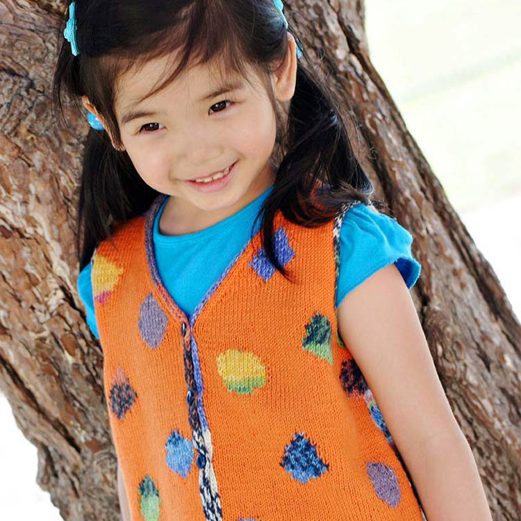 Girl in pigtails wearing orange vest with colourful shapes.