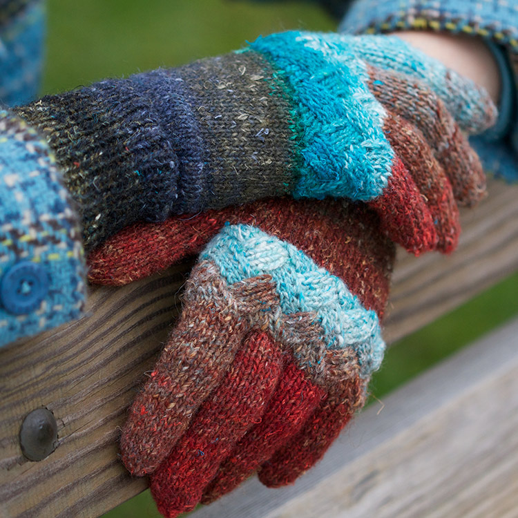 Adult gloves in a gradient yarn with an entrelac band around the knuckles.