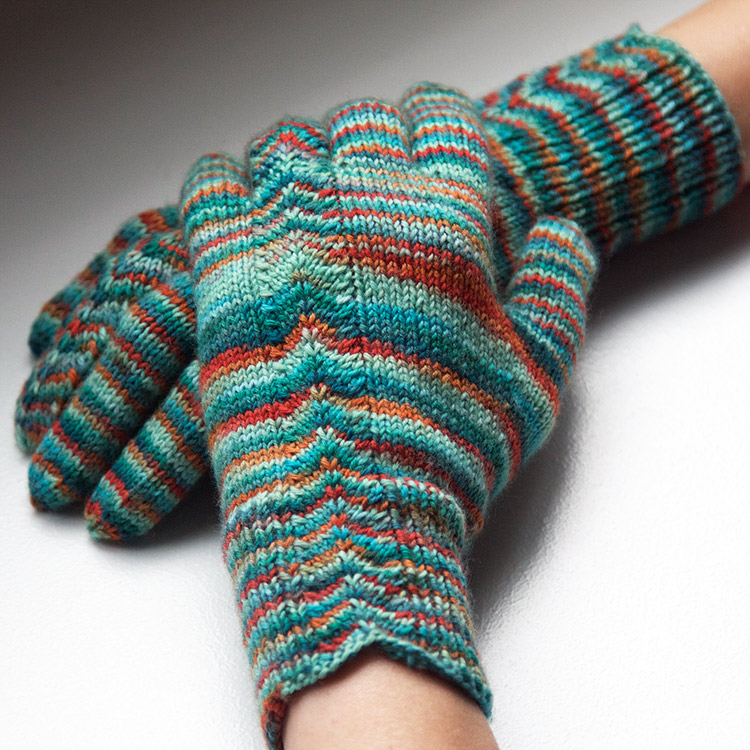 Gloves with a chevron pattern running from the cuff, up the back of the hand, and up the ring finger.