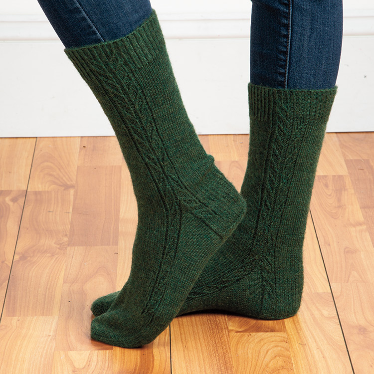 Top down socks with twisted stitch detailing running down side of leg and splitting to round down side of foot and side of heel.