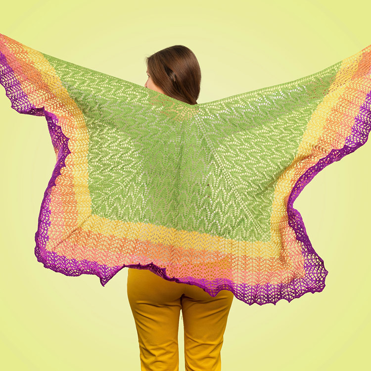 Three-quarter lace shawl held up and viewed from back. Edges, worked in bands of colour, are fluttering with movement.