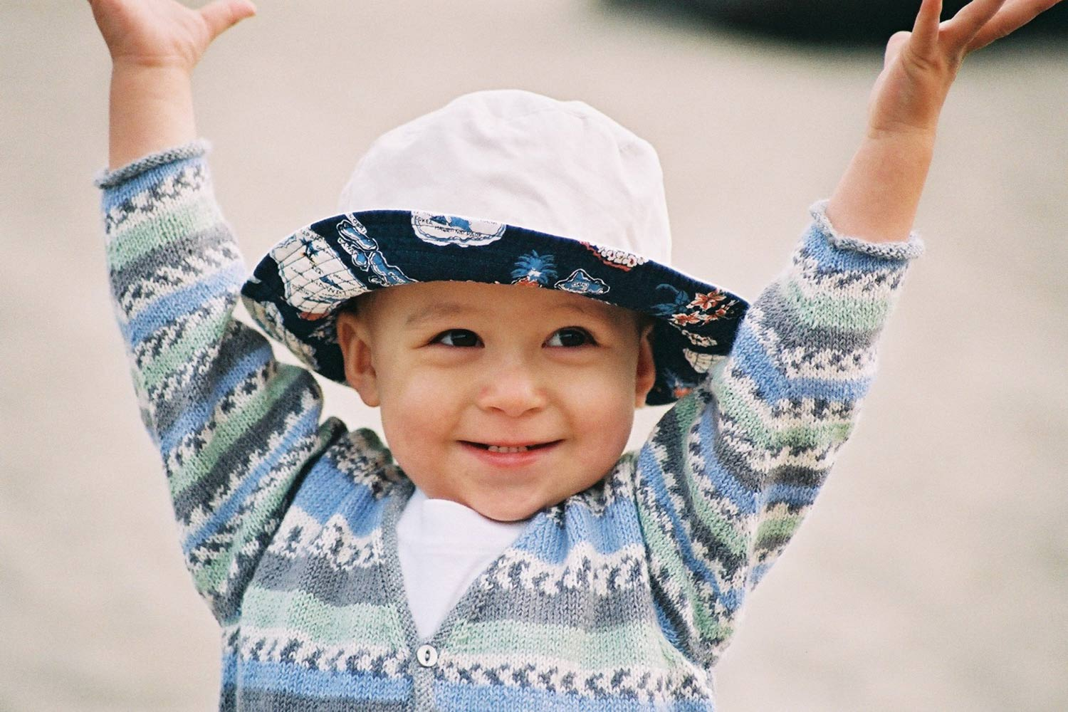 Head and shoulders view of toddler with arms up, wearing a v-neck, long-sleeved cardigan.