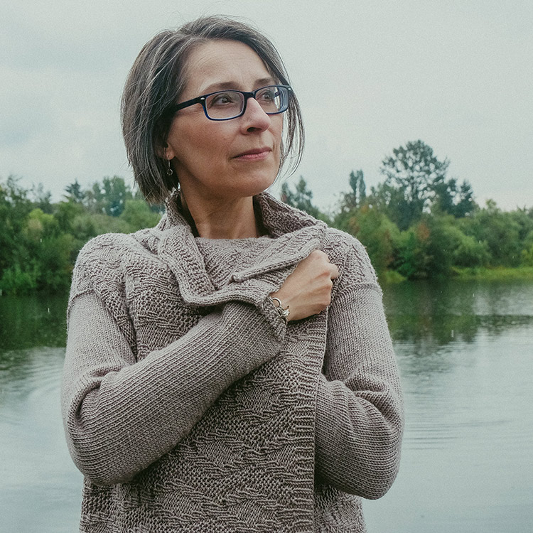 Woman holding the fronts of a long textured cardigan and hugging them to herself and creating a dynamic collar.