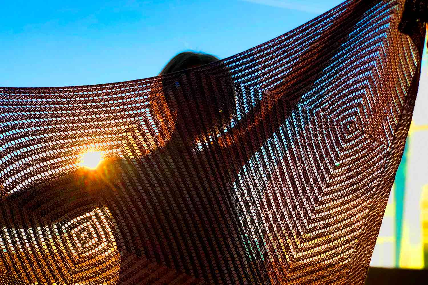 Person holding up a triangular shawl with sunlight shining through it highlighting the concentric squares created by the eyelet stitch pattern.