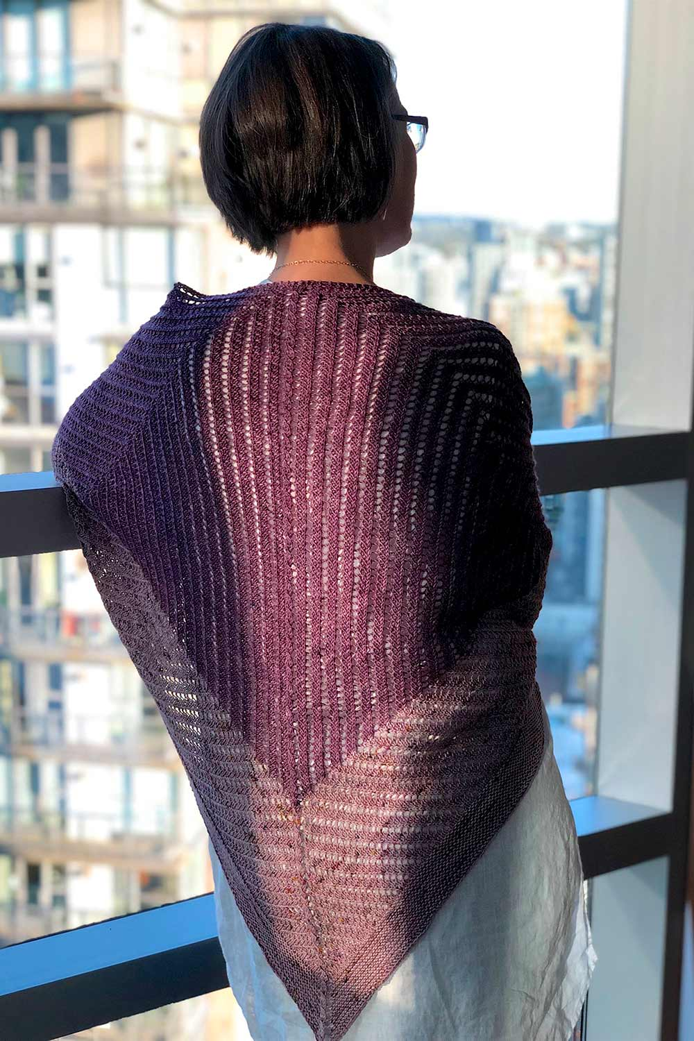 Two-tone triangular shawl draped over shoulders and hanging down back. Stitch pattern bends 90 degrees at the colour change.