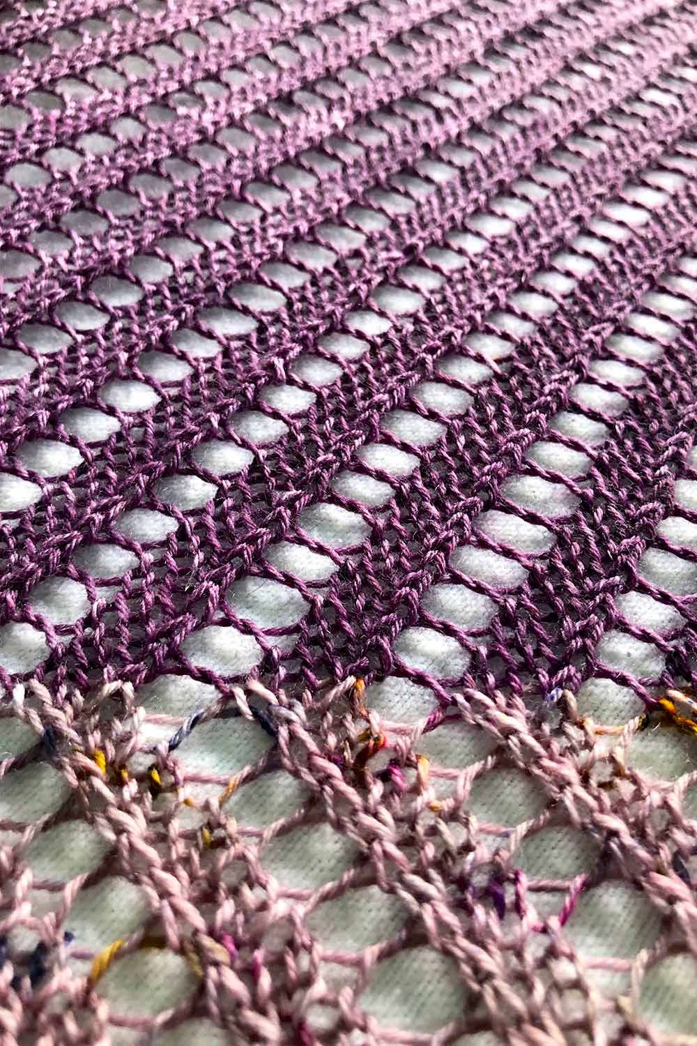 Detail of rows of light purple with diagonal lines of lace that change direction when the colour changes to dark purple.