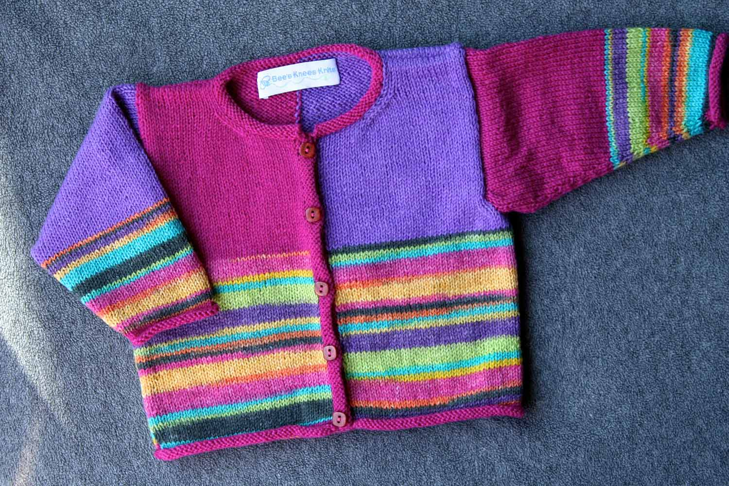 Baby cardigan in brightly coloured stripes and purple and pink colour blocks.