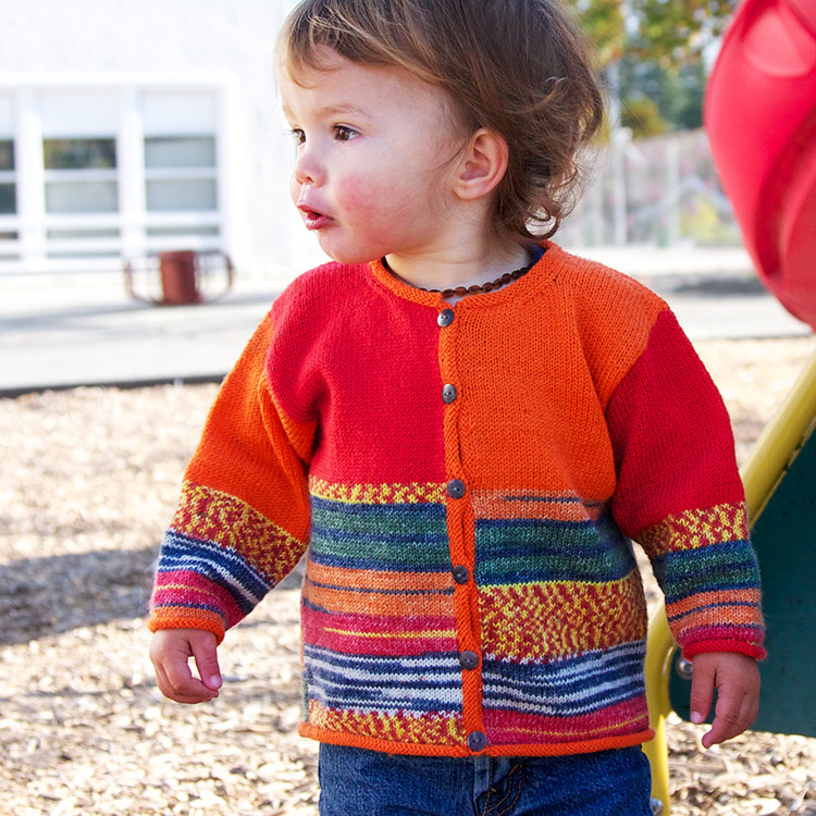 Toddler in a colour block cardigan with self-patterning yarn on lower sleeves and lower body.