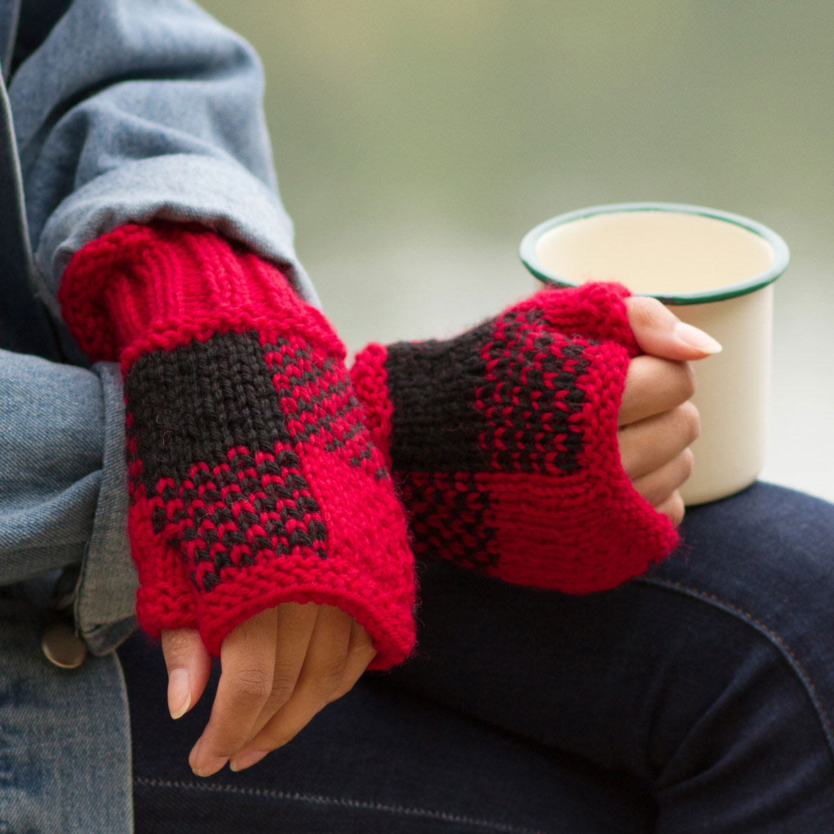 Hands crossed on lap, one hand holding a cut of cocoa and both wearing red and black checkered fingerless mitts.