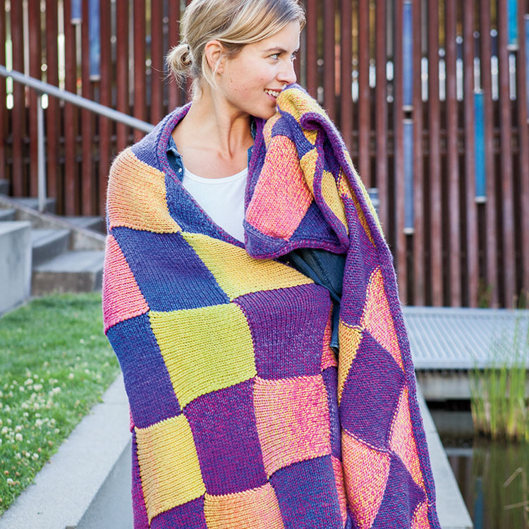 Woman hugging colourful blanket around herself sporting large squares/diamonds of alternating colours in gradient yarn.
