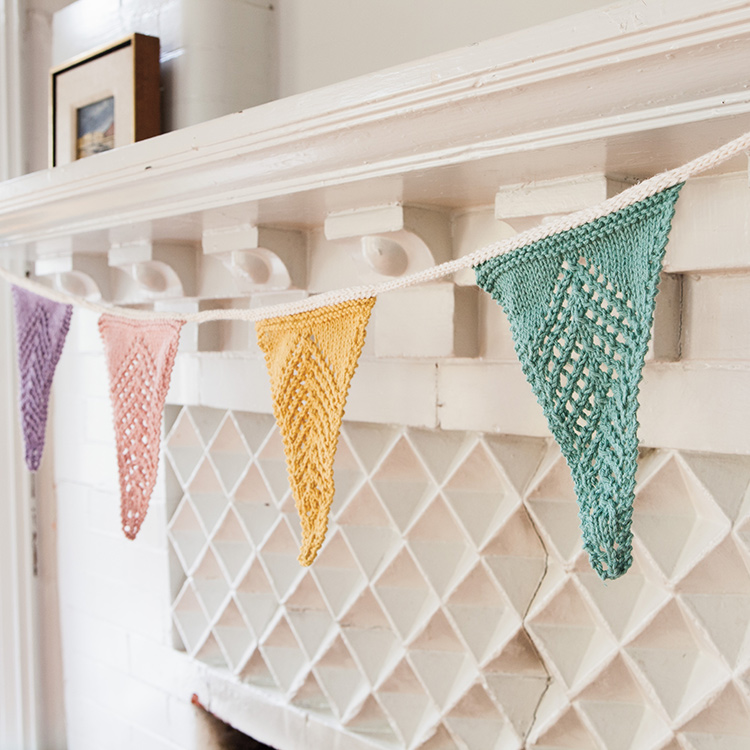Triangular knitted bunting flags with reverse chevron eyelet motif hanging from a mantle.