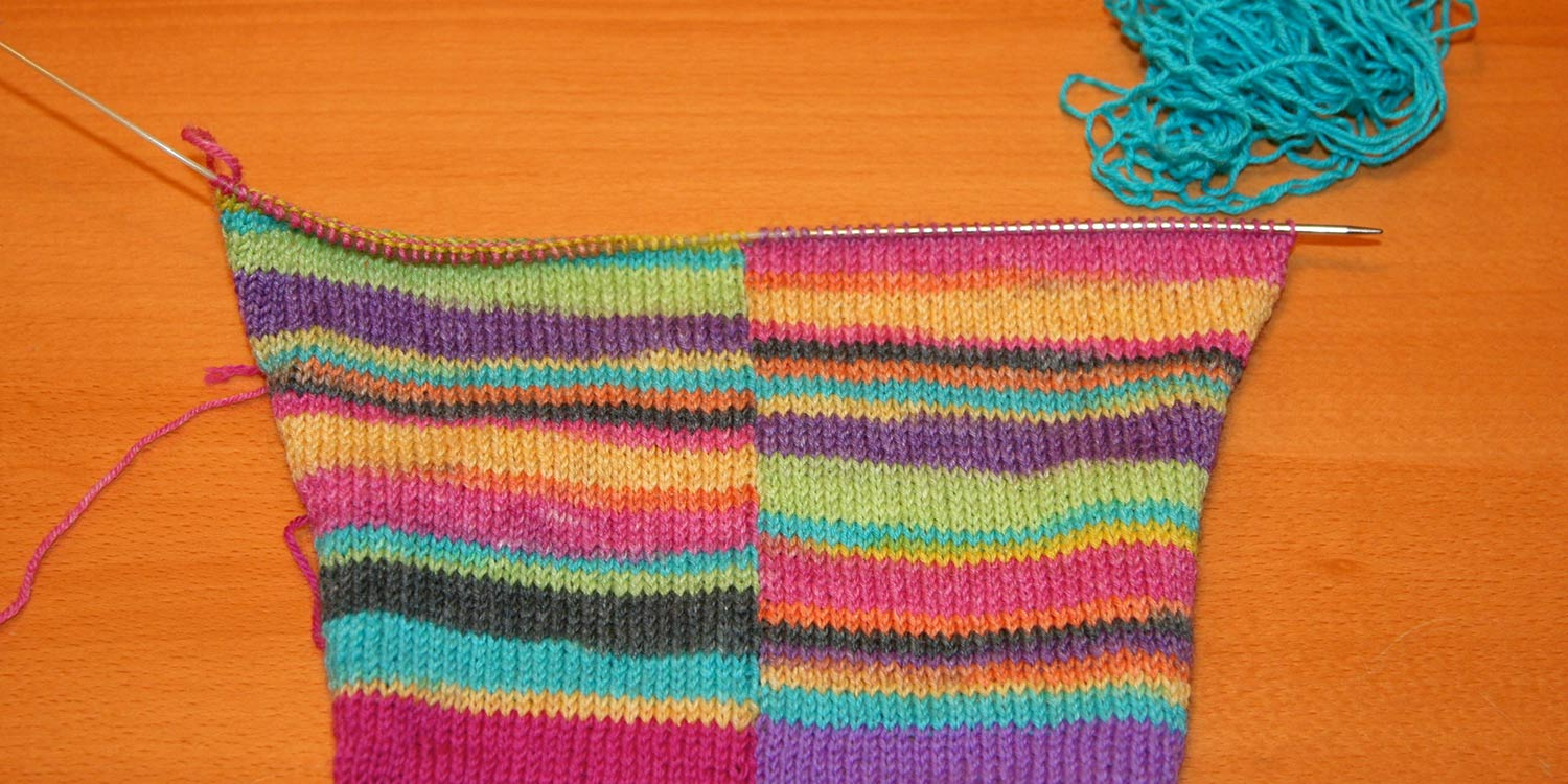 Unravelled hem is in a heap of turquoise yarn and live stitches are one a knitting needle.