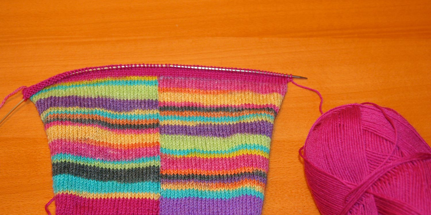 Several rows of pink hem have been worked from the top down.