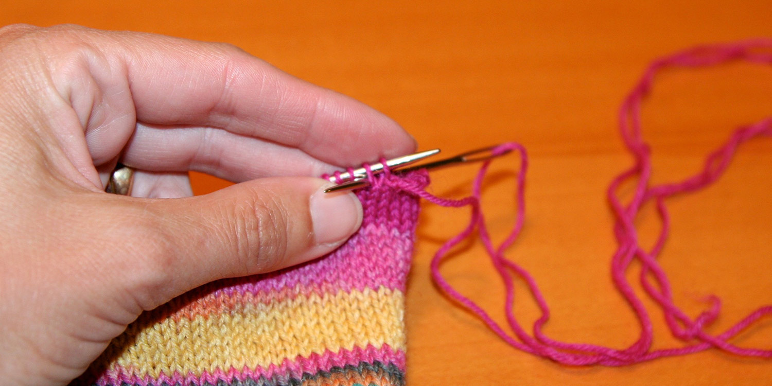Yarn extends from first stitch on left needle while tapestry needle is inserted purlwise into first two stitches on needle.