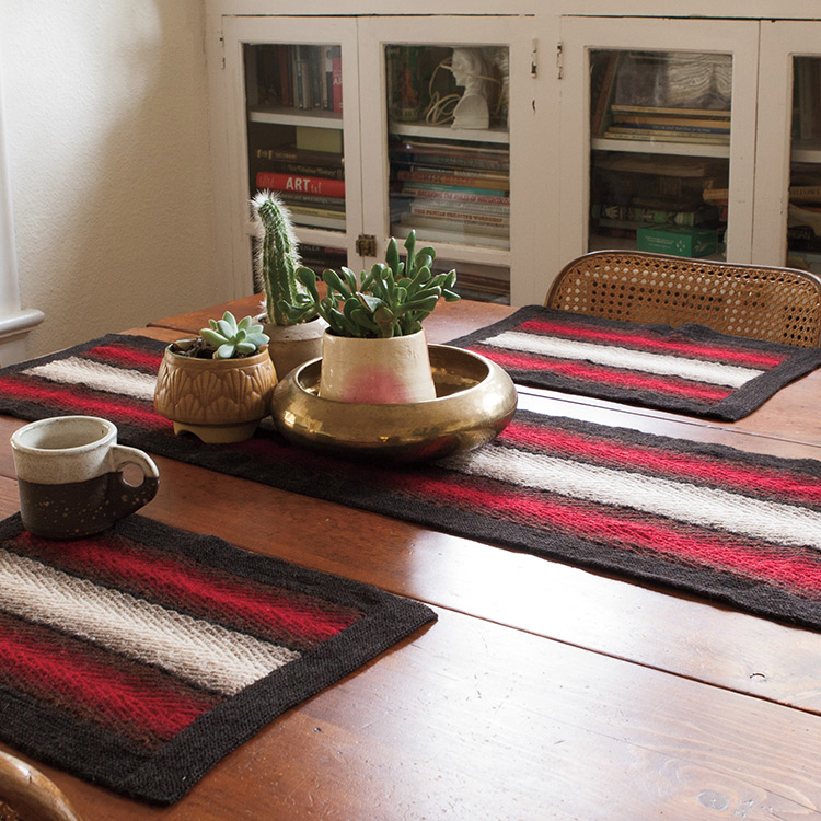 Table set with placemats and table runner worked in textured woven knit stitch in gradient coloured stripes.