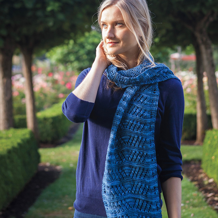 Lace scarf draped once around neck and hanging down past waist.