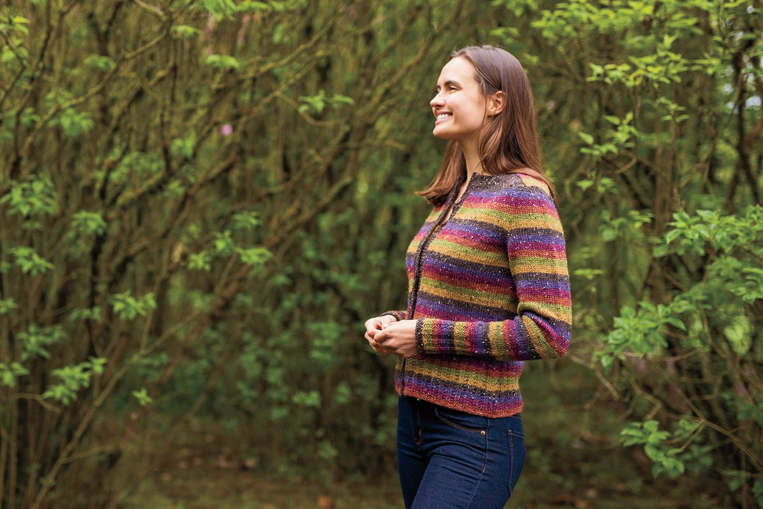 Side view of woman in the woods. She's wearing a striped cardigan with saddle shoulders.