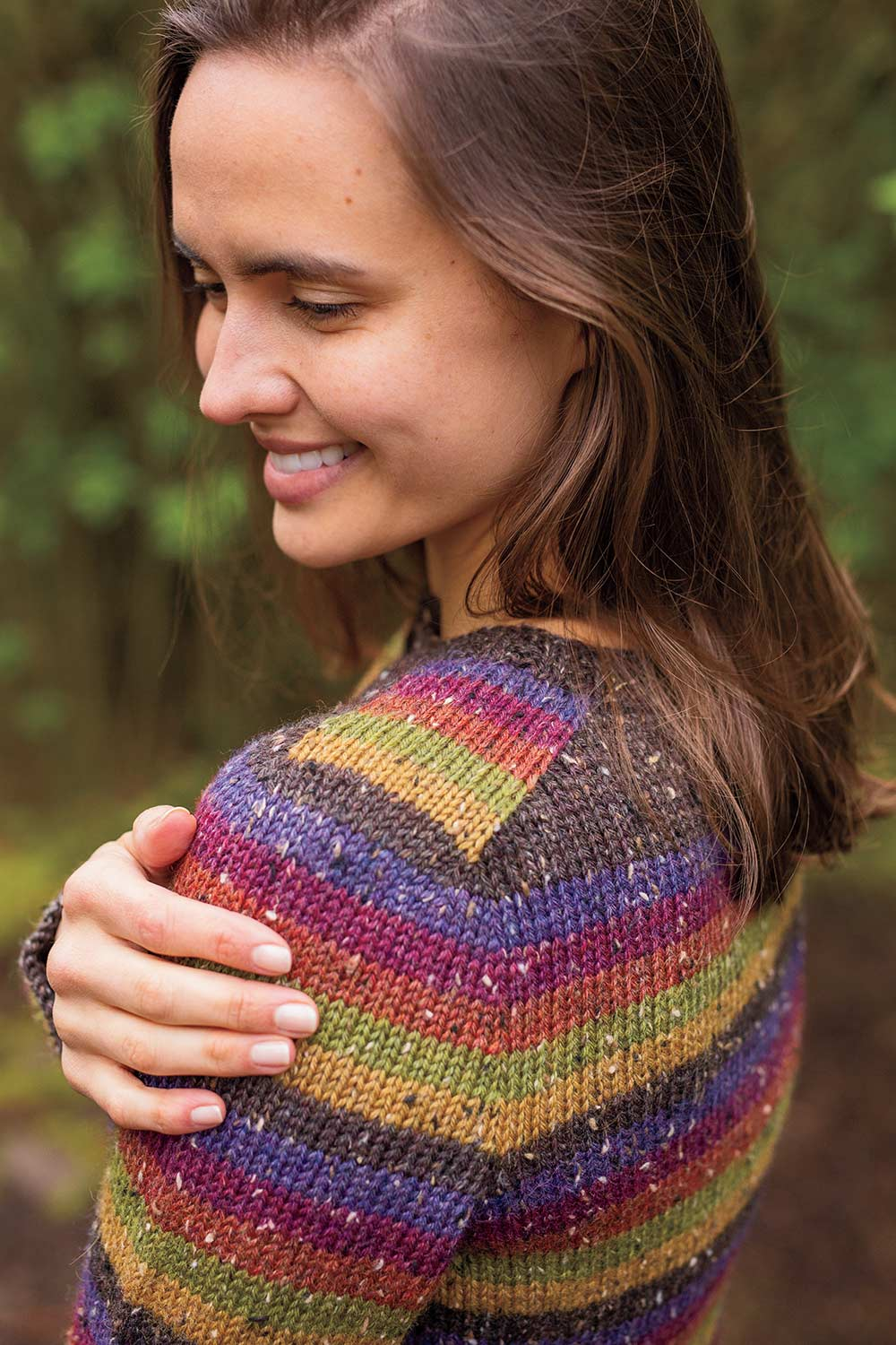 View of striped saddle shoulder showing the unbroken stripe progression beginning at the neck and running down the sleeve. Sweater is worked top down.