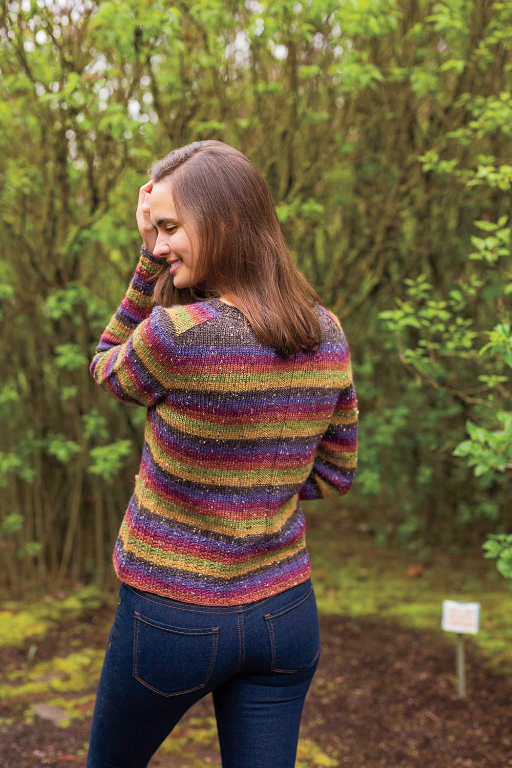 Back view of striped cardigan with saddle shoulder which is also striped. Upper back through shoulder and neck shaping is a solid colour which rest of sweater is striped.