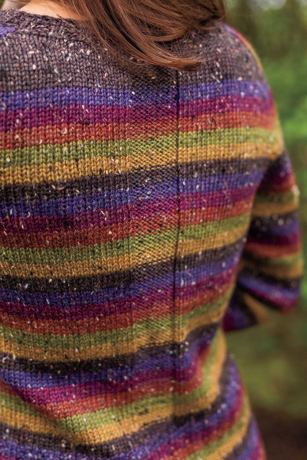 Back view of a colourful striped sweater showing a vertical stripe of reverse stocking stitch running down back breaking up the coloured stripes.