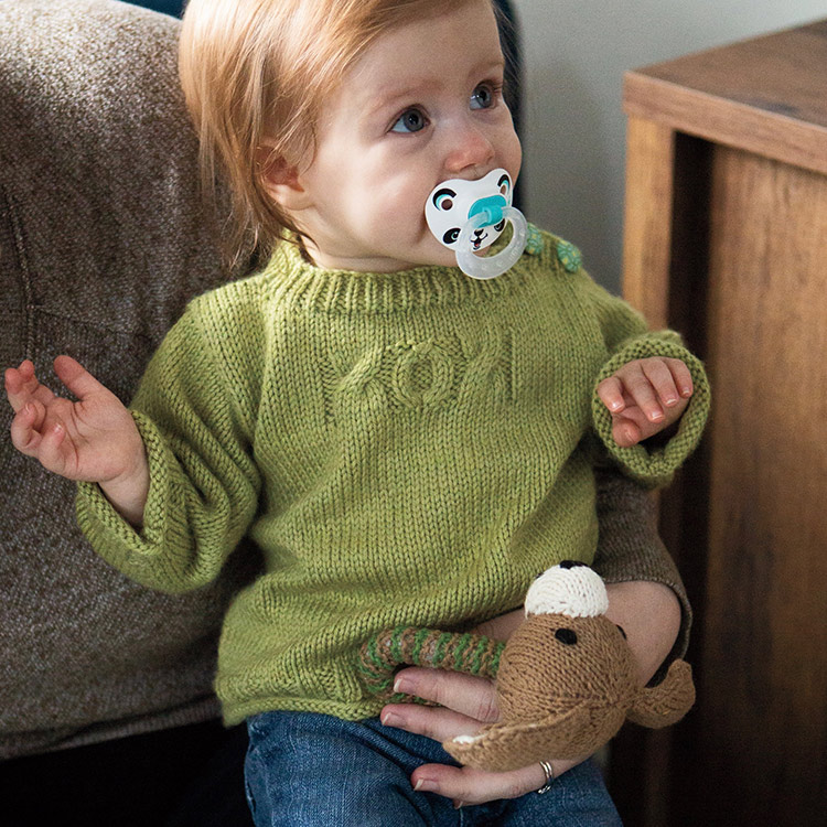 Baby in a pullover with buttons at the neck and cables across the chest spelling out XOX.